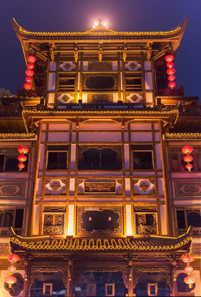Traditional chinese building ailluminated at night in Hongya cave, Chongqing, China