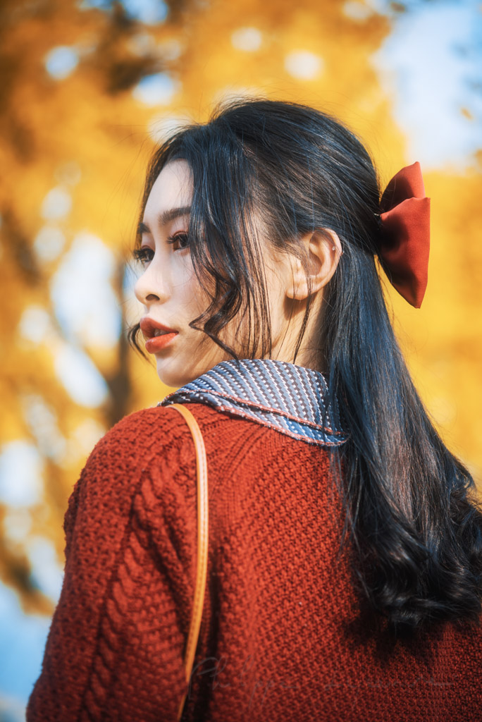 Young chinese woman wearing a red knit jumper portrait against yellow gingko leaves in autumn in Chengdu, Sichuan province, China