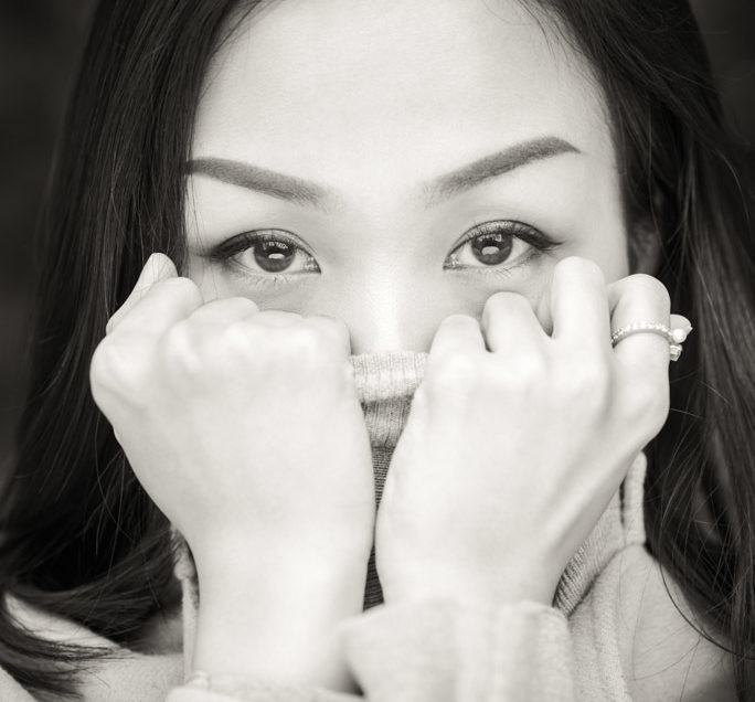 Young chinese woman with long black hair looking at the carmera wearing a turtleneck sweater and holding it with her hands in front of her mouth black and white close-up portrait. in Chengdu, Sichuan province, China - Model : Fanny