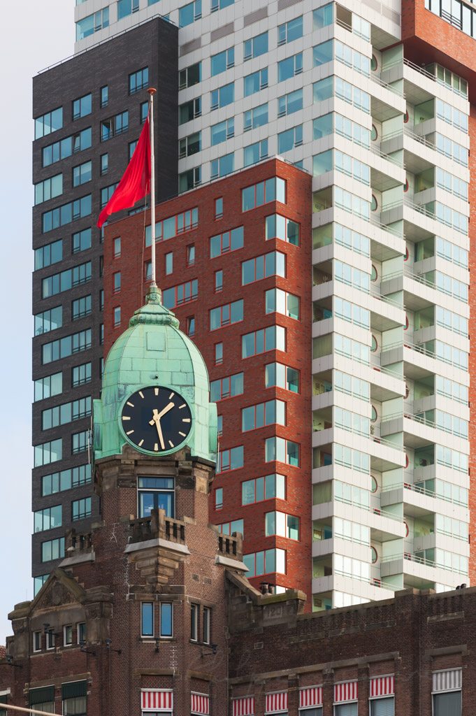 Rotterdam, Netherlands : Clock tower on the New York Hotel with a modern building in the background in Wilhelminapier district.
