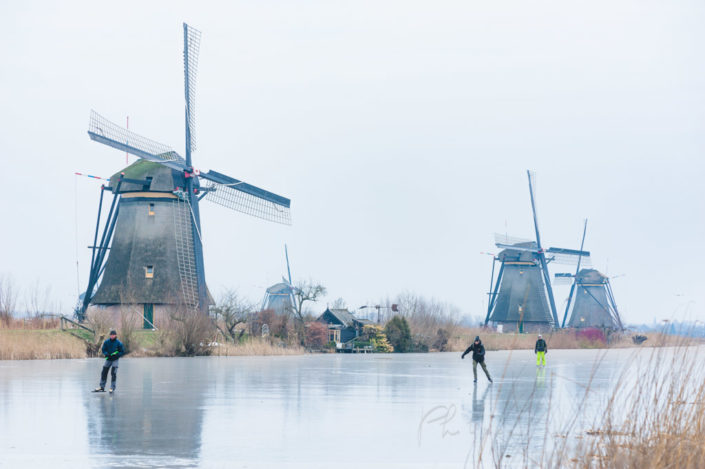 Ice skaters and Windmills in winter with frozen water in a canal in Kinderdijk, Netherlands