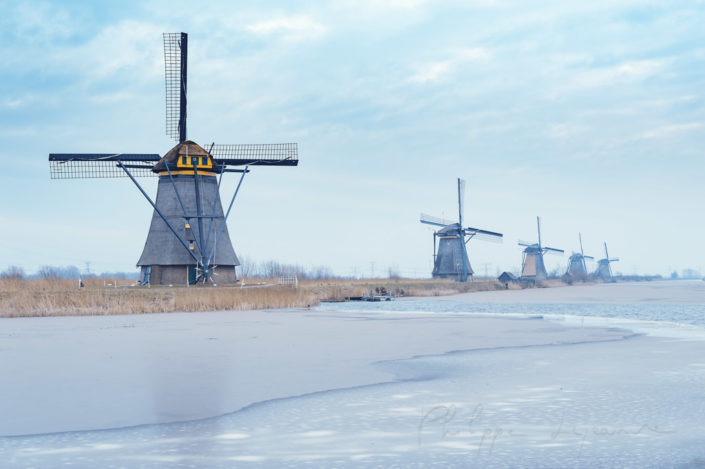 Windmills in winter with frozen water in a canal in Kinderdijk, Netherlands
