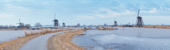 Windmills in winter panorama with frozen water in a canal in Kinderdijk, Netherlands