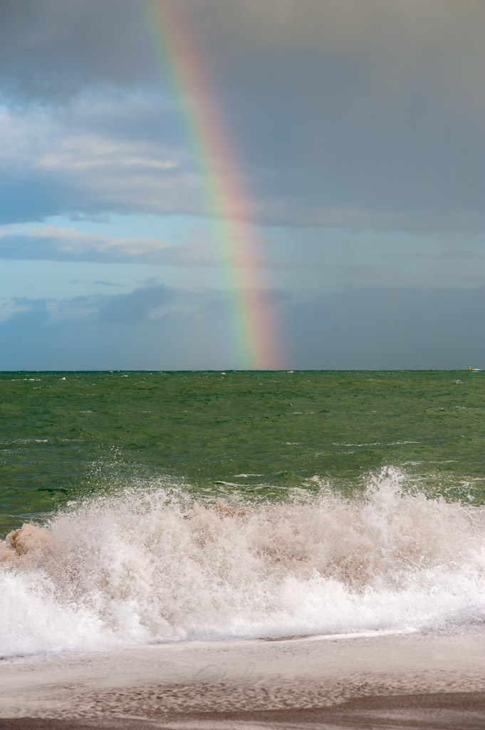 Rainbow above the sea with sea-foam in the foreground, Saint-Malo, Brittany, France
