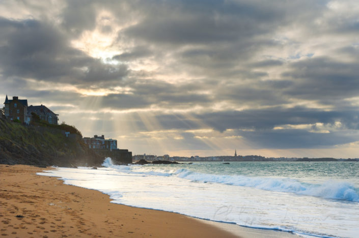 Saint-Malo beach in windy weather with sunrays passing through the clouds, Brittany, France