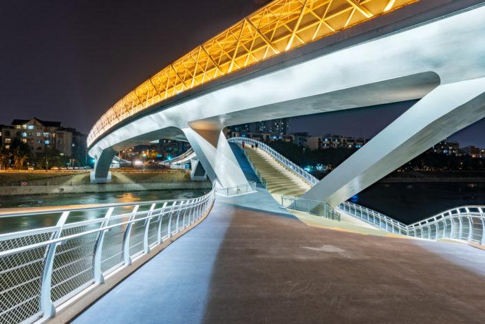 Twisted modern bridge illuminated at night abobe the river, Chengdu, Sichuan province, China