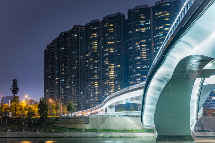 Twisted modern bridge illuminated at night with skyscrapers in the background, Chengdu, Sichuan province, China