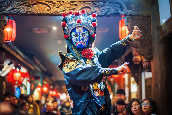 Chengdu, Sichuan Province, China : Chinese actor performs a public traditional face-changing art or bianlian onstage at Chunxifang Chunxilu covered street.