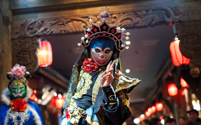 Chinese actor performs a public traditional face-changing art or bianlian onstage at Chunxifang Chunxilu covered street, Chengdu, Sichuan province, China