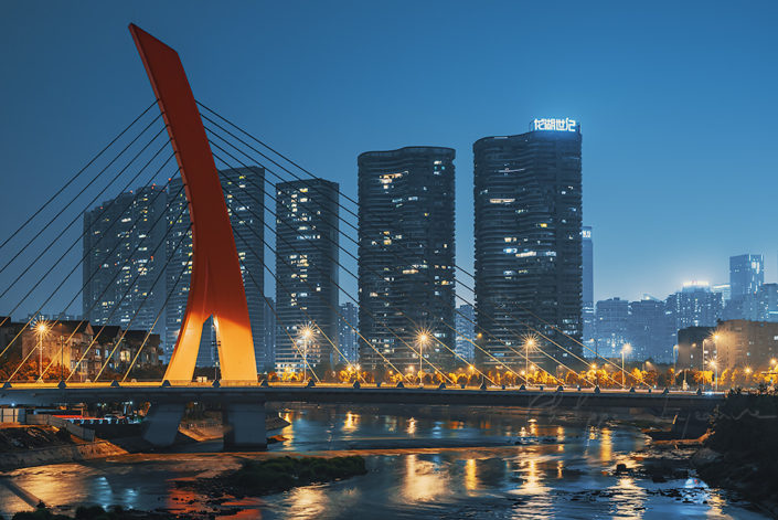 ShiJiChengLuKuaFuHeDaQiao red cable bridge illuminated at night against skyscrapers in Chengdu, Sichuan province, China