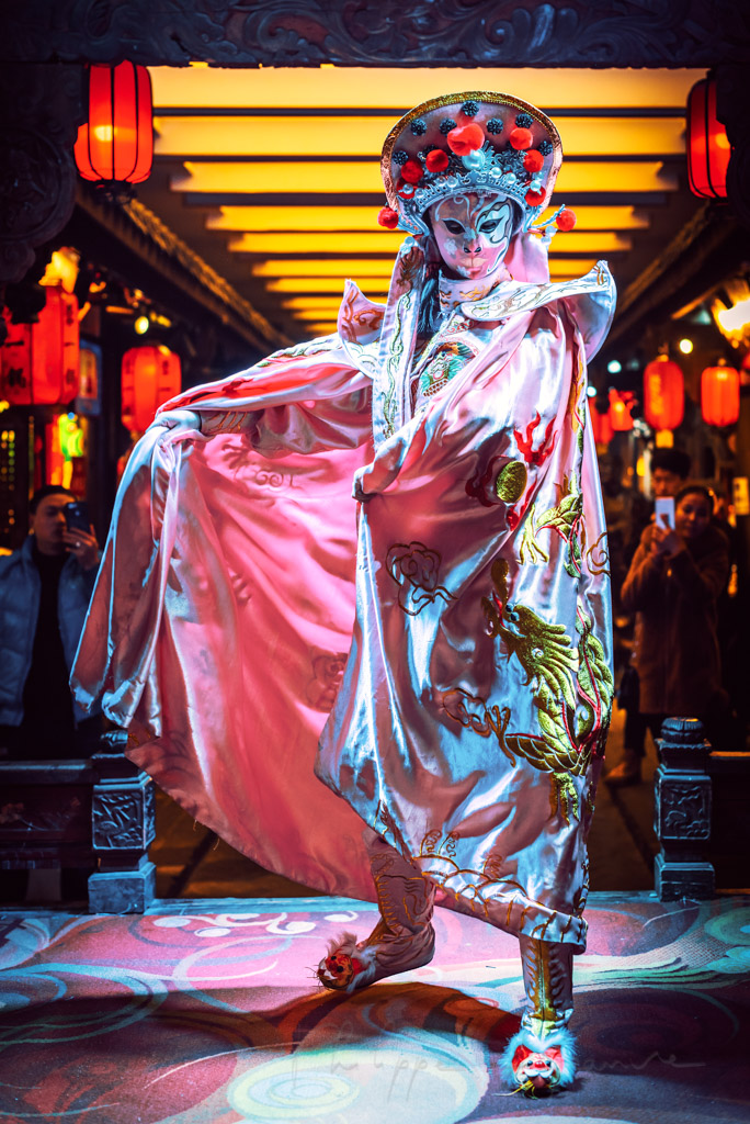 Chinese actress performs a public traditional face-changing art or bianlian onstage at Chunxifang Chunxilu covered street, Chengdu, Sichuan province, China