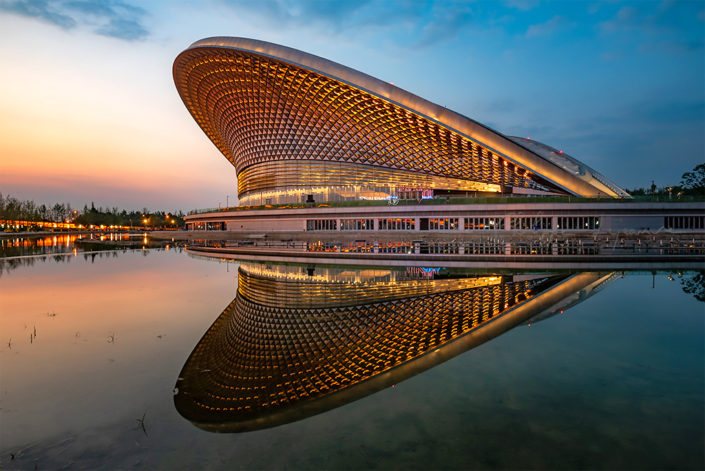 Chengdu open air music park modern building with futuristic architecture reflecting in a pond at blue hour, Sichuan province, China