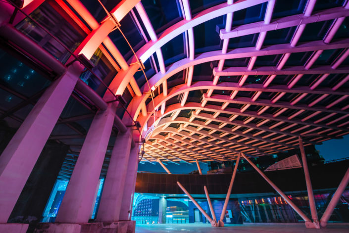Umbrella shape architectural feature illuminated with multicolor lights at night