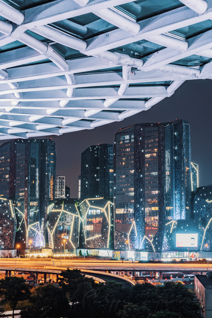 Umbrella shape architectural feature illuminated with multicolor lights at night in XinNanZhongXin building and KaideTianFu square buildings in the background in Chengdu, Sichuan province, China