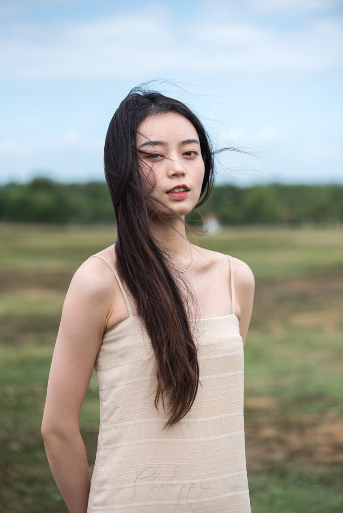 Chinese young woman in a field portrait in Chengdu, Sichuan province, China