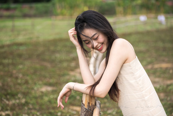 Chinese young woman portrait in nature near a fence in a field, in Chengdu, Sichuan province, China