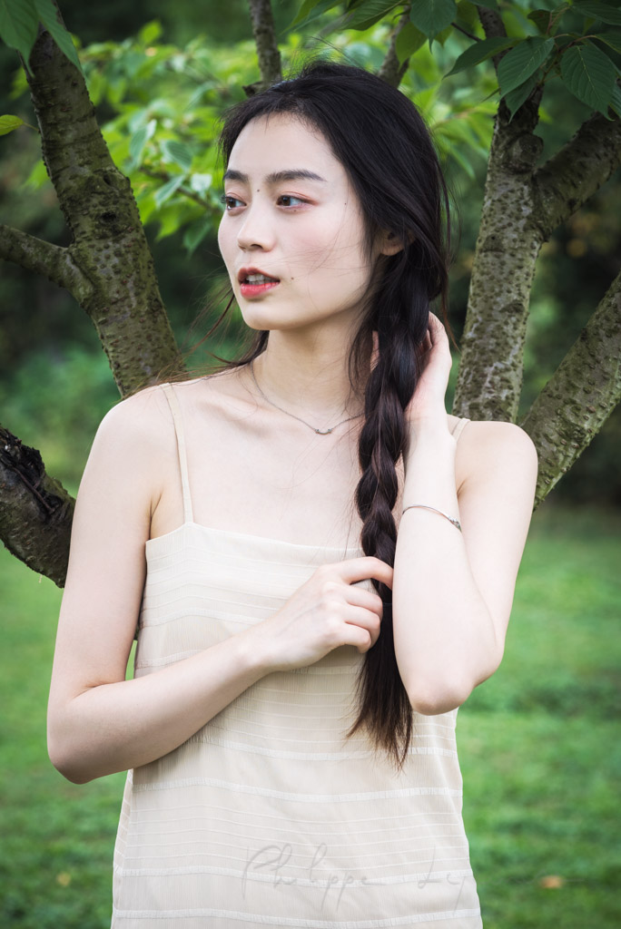 Chinese young woman playing with her hair in nature in Chengdu, Sichuan province, China