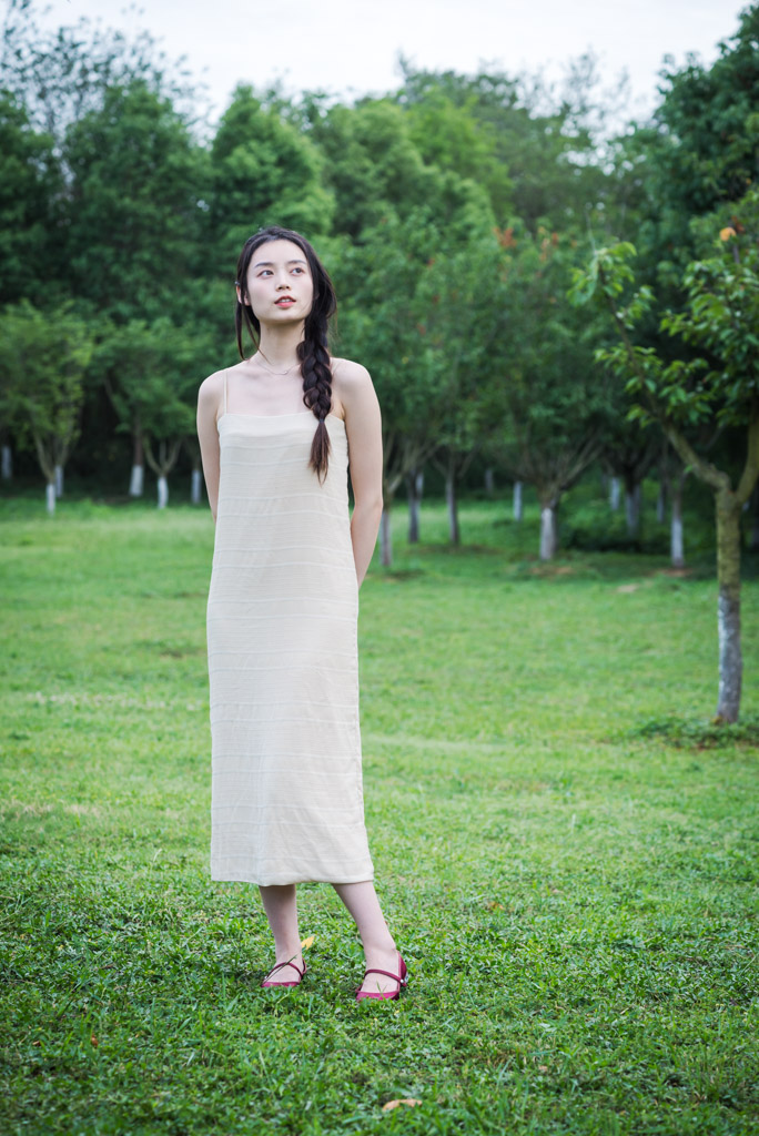 Chinese young woman standing on grass surrounded by trees in Chengdu, Sichuan province, China