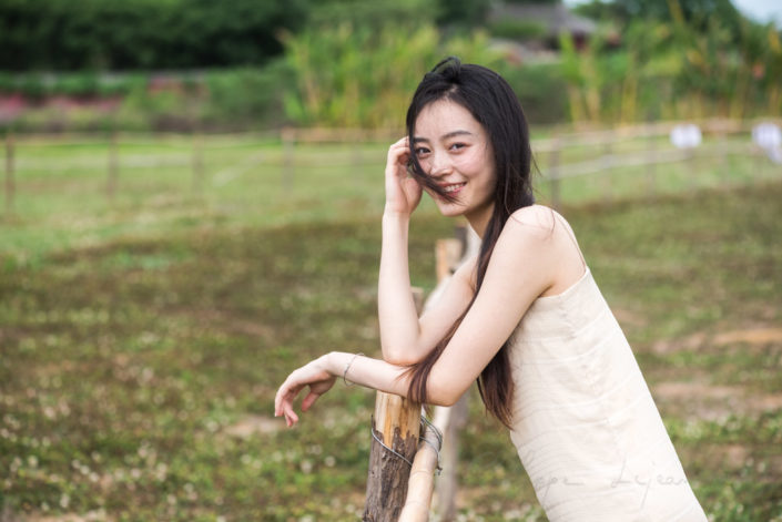 Chinese young woman portrait in nature near a fence in a field in Chengdu, Sichuan province, China