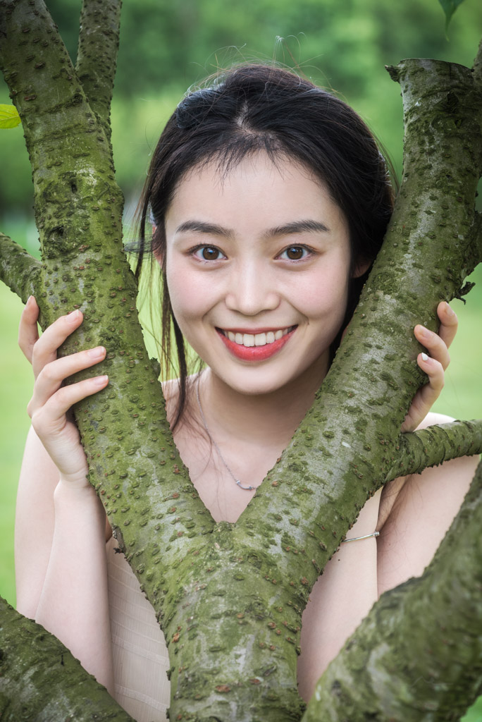 Smiling chinese young woman holding a tree in nature in Chengdu, Sichuan province, China