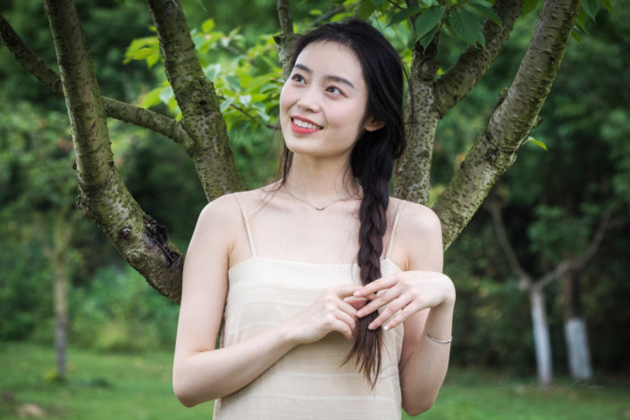Smiling chinese young woman playing with her hair in nature in Chengdu, Sichua province, China