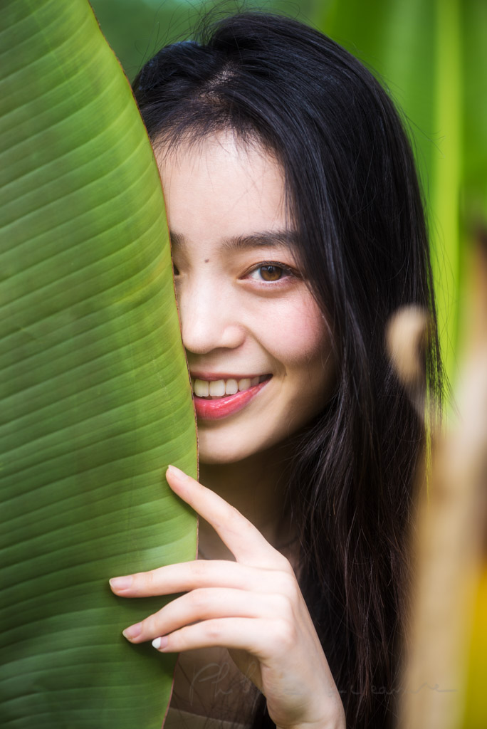 Chinese young woman portrait behind a leaf in nature, Chengdu, Sichuan province, China