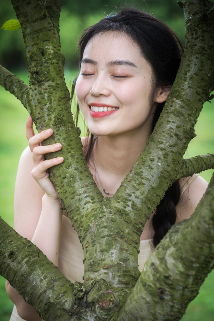 Chinese young woman holding a tree in nature, Chengdu, Sichuan province, China