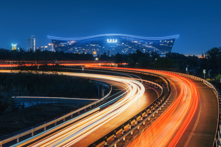 Chengdu New Century Global Center building at night with car light trails in the foreground, Sichuan province, China