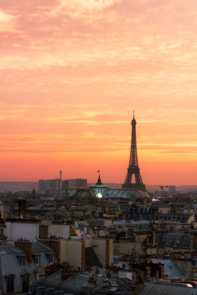 Eiffel tower, Grand Palais and roofs at sunset in Paris, France