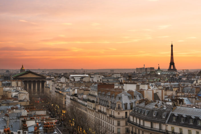 Eiffel tower, roofs and city skyline in Paris, France at sunset