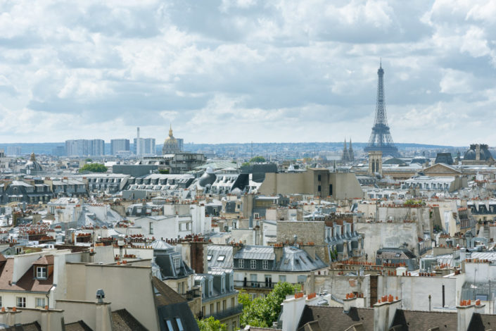 Paris roofs with the Eiffel tower under a cloudy sky