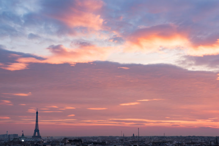 Paris skyline with purple clouds at sunset, France