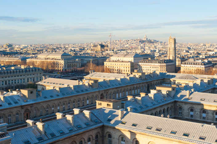 Roofs of Paris with Montmartre in the background on a sunny evening, France
