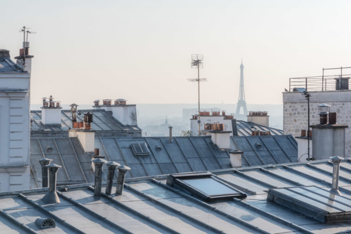 Distant view of the Eiffel tower from rooftops on a sunny day in Paris, France