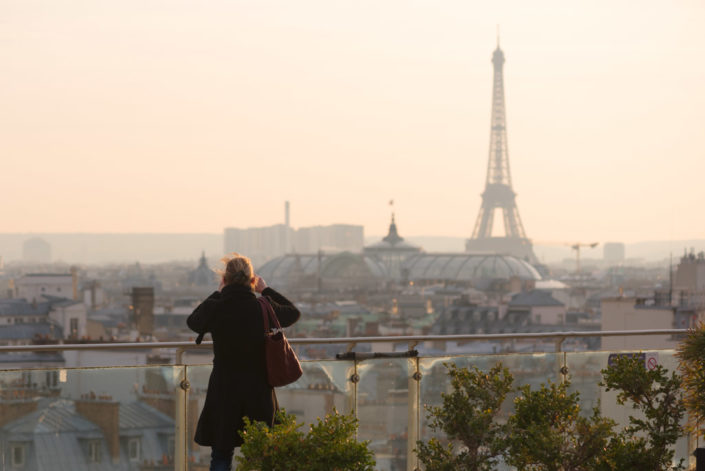 Woman taking the Eiffel tower in photo from an elevated point of view in Paris, France