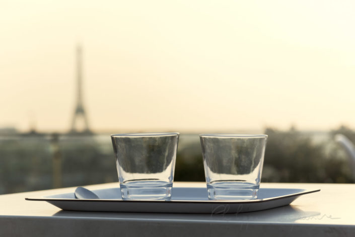 Two glasses on a plate with the Eiffel tower in the background in Paris, France.