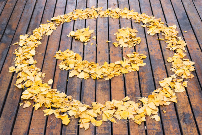 Smiley drawn with yellows leaves on a wooden ground in autumn