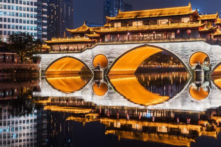 Anshun bridge illuminated at night and reflecting in JinJiang river in Chengdu, Sichuan province, China