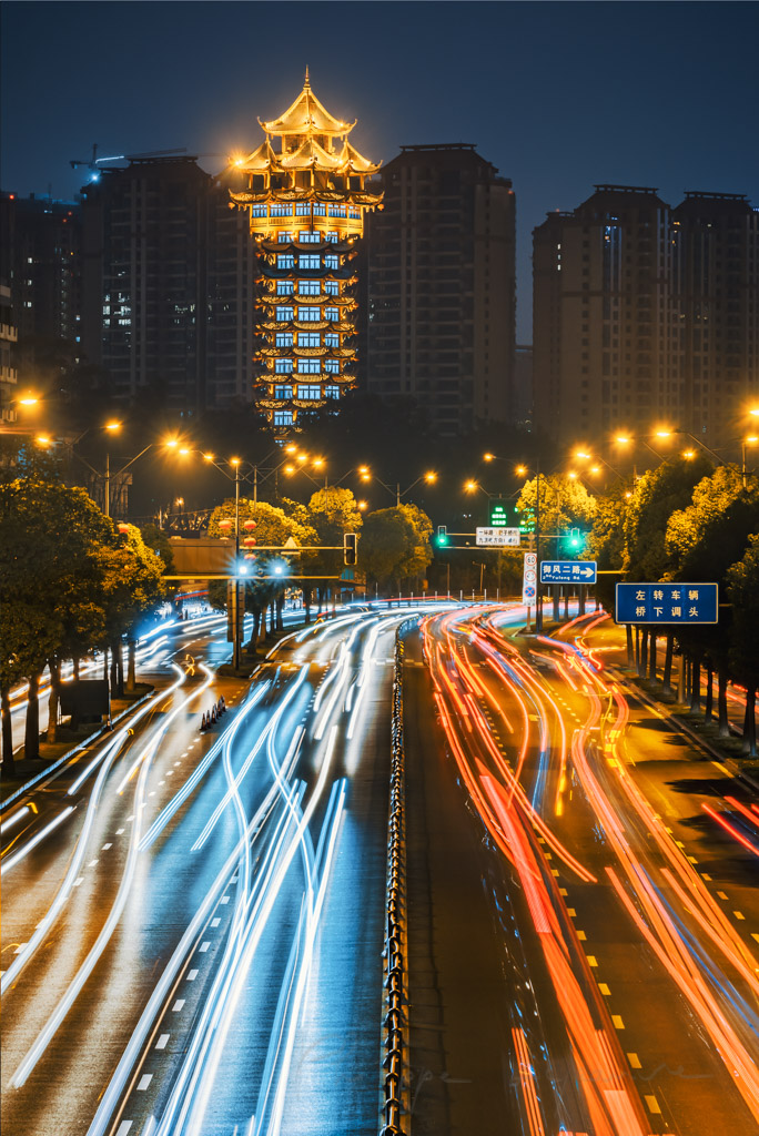 Jiutian tower illuminated at night with car traffic light trails in Chengdu, Sichuan province, China