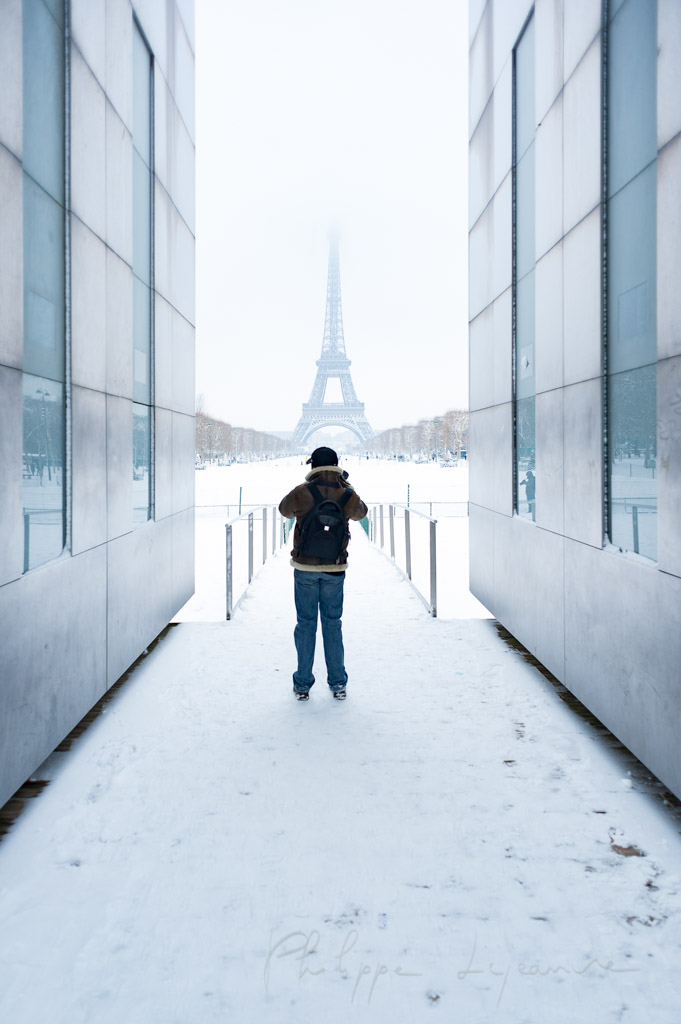 Man taking in photo the Eiffel tower under the snow in Paris, France