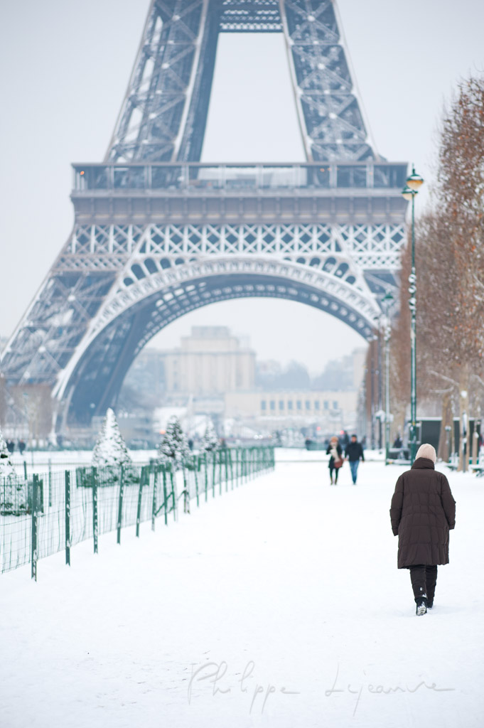 Woman walking by the Eiffel tower under the snow in Paris, France