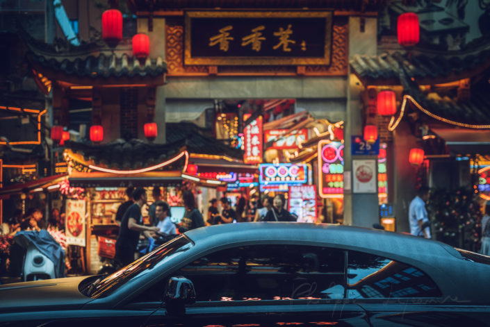 Black car in front of chinese traditional gate in Xiangxiang touristic alley at night, Chengdu, Sichuan province, China