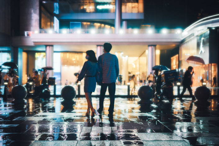 Couple walking near IFS at night under the rain in Chengdu, Sichuan province, China