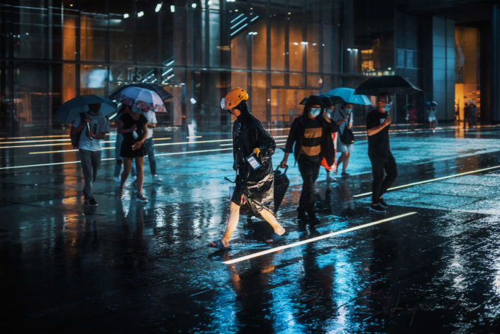Delivery man rushing in the street under the rain at night near International Finance Square - IFS -, Chengdu, Sichuan province, China
