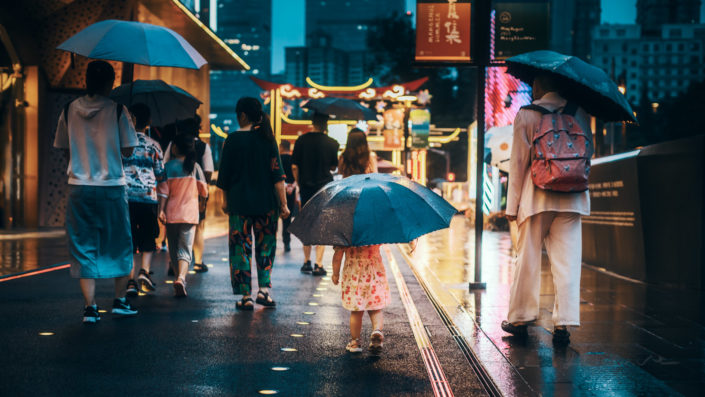 Little girl with a big umbrella wlaking with people under the rain at night in the city, Chengdu, Sichuan province, China