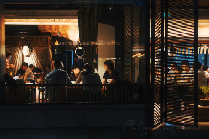People eating in a restaurant near Taikooli at night in Chengdu, Sichuan province, China