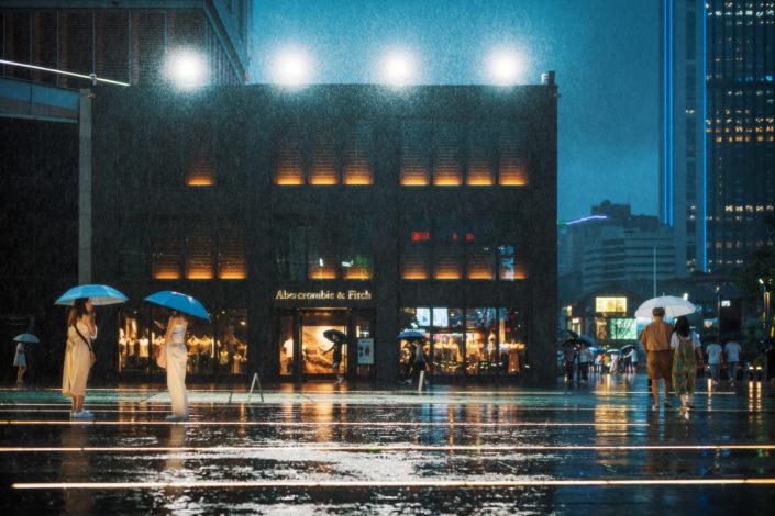 People walking around International Finance Square -IFS- under the rain at night, Chengdu, Sichuan province, China