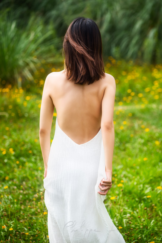 Young Chinese woman wearing a white dress in nature in Chengdu, Sichuan province, China