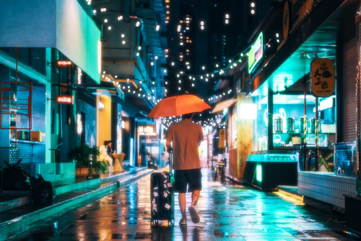 Young traveller with luggage in an illuminated street at nighty under the rain, Chengdu, Sichuan province, China