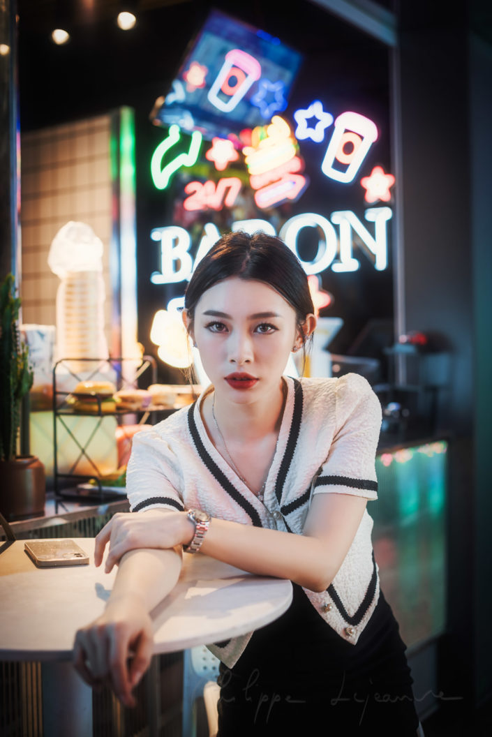 Young chinese woman sitting at a table with neon lights in the background in Chengdu, Sichuan province, China